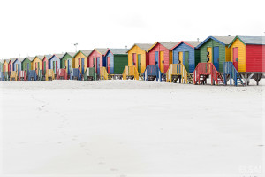 Colorful beach huts in a row on the beach in winter painted red, green; blue; and yellow